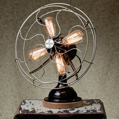 """A Fan-tastic Lamp. This steam-punk inspired lamp is made from a 1939 Signal Fan bringing old style and new purpose together. It's got a black body, with metal cage, brass fittings, a wooden base, and comes with four reproduction Edison light bulbs.   Dimensions:18""""W x 21""""T x 11""""D"""