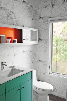 In the new powder room, Jill Malek wallpaper adds graphic punch to custom cabinetry.  Photo by Brent Humphreys.
