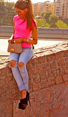 Trending Casual Style.  Neon hot pink top, ripped jeans, black stiletto high heels with a hidden platform worn by a pony-tailed model sitting on a wall looking in her beige purse.