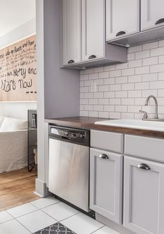 Matte metro tiles backsplash and grey kitchen: San Antonio Gray (Benjamin Moore) and unfinished cabinet from the Kitchen Cabinet Depot