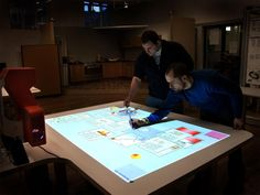 "The Promethean Table is a pen based ""multi-touch"" collaborative surface, based on the promethean whiteboard technology, each pen is able to be used simultaneously, and is also uniquely identifiable.    The physical table was created in Culture Lab and has the promethean technology inside."