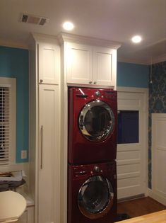 Red LG stacked washer/dryer; laundry area in kitchen, crown molding