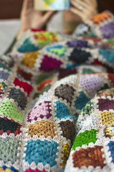 Crochet blanket w/ colourful squares on a white background