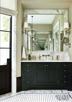 bathrooms - marble tiles floor tan walls black single bathroom vanity marble slab top backsplash marble framed mirror wall-mount faucet  Glam
