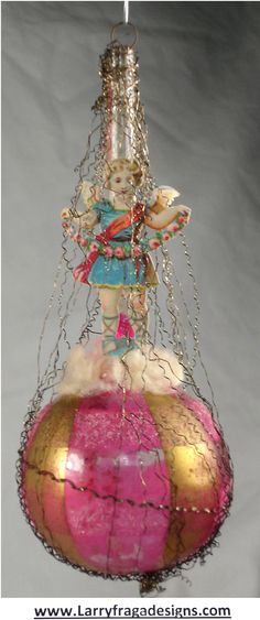 BALLOON WITH SCRAP ANGEL  Dimensions: 5 1/4''   Description: Beautiful early Victorian balloon. Unsilvered, pink and gold ball. Standing on top of cotton is a standing, full figured scrap lithograph Angel with garland.