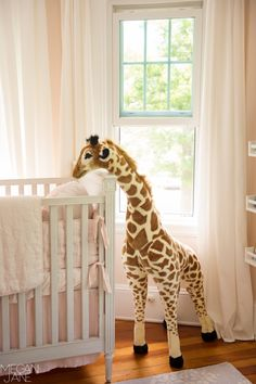 Giraffe peeking over the Emilia Crib at baby! #rhbabyandchild #fallinlove