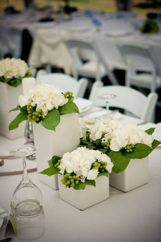 White wedding décor ....  Ever notice how white makes all other colors POP?  Here the white hydrangeas and white floral containers provide the perfect counterpoint to green leaves and berries.  CLASSIC CONTEMPORARY at it's best!
