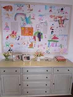 artwork displays on a large corkboard