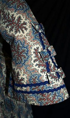 "Orange, Red & Blue floral sprays on cream wool challis background. [Roller print?] Mostly hand sewn. Piped at waist & armscyes, has original brass hooks with handmade round eyeholes. Bodice fully lined with cream linen and openings are lined with brightly printed calico. Skirt has cartridge pleating, hem edged with blue hem protector, has deep right side pocket, skirt lined with cream & brown polished cotton. Bust: 30""; Waist: 22""; back length of gown: 57"". [Remade 1850s?] By pseitas via Flickr."