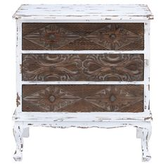 Create a stylish vignette or stow small trinkets in your entryway with this distressed wood cabinet, showcasing 3 carved drawers and a white finish.