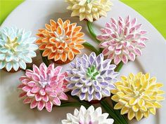 Cut mini marshmallows in half diagonally. Put in plastic bag with decorative sugars. Shake. Sugar only sticks to cut part. Let them sit and petals will puff up again. Attach with icing on cupcake