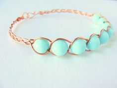 Love the aesthetics of braiding thin wire around beads; so simple yet beautiful