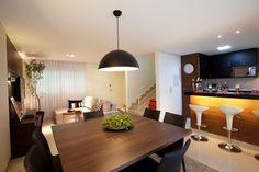 Um dos desafios da designer de interiores Sylvia Leticia de Araujo ao projetar este espaço, de 35,4 m², foi integrar a cozinha com a sala de TV, o bar e a sala de jantar. Para que essa junção fosse graciosa, a profissional escolheu revestir o balcão da cozinha com painel amadeirado, que se assemelha à decoração do resto do ambiente.