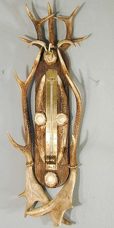 an antler thermometer with a carved deer head made of horn