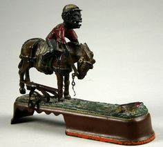 ca 1879-1900; A. J. & E. Stevens Always Did 'Spise A Mule cast-iron mechanical bank. This jockey version of this popular bank has excellent action. When a coin is placed in jockey's mouth and lever is pushed, mule bucks throwing jockey overhead and as jockey's head hits the log below, coin drops into base;