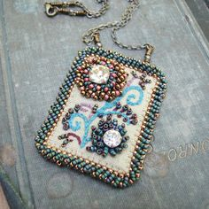 Embroidered linen pendants on brass chain