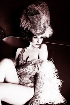 Burlesque star Dita Von Teese in marabou feather showgirl costume with top hat.