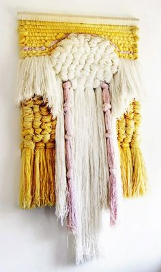 Knotted yarn textile wall hanging in yellow and white very 1970s .