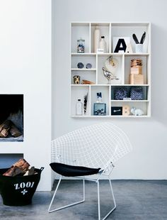 Love that shelf display. #shelf #vignette #Bertoia #wire #chair #fireplace #white #blue