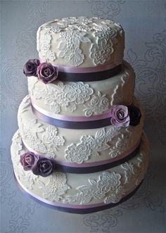 Oh so pretty lace wedding cake with purple sugar roses. For more purple wedding ideas, go to the Squidoo website and then add at the end of the link:  /purple-themed-wedding
