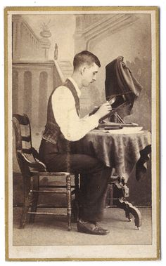 """ca. 1860-70s, [carte de visite portrait of a young photographer who appears to be hand coloring or retouching his work; hand written on verso """"Photographer stranger""""] via Capitol Gallery, Cabinet Cards"""