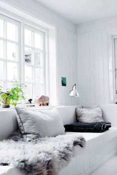 That's a great white sofa. This living room (or at least I think that it's a living room) is a great choice if you love light colours. The combination with grey and black is a must!