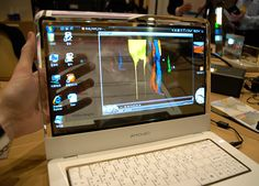 The group behind the OLED display technology was showing off this pretty neat concept laptop that features a see-through AMOLED display. Anyone who's ever had to look around their laptop screen in order to see their TV will immediately see the benefits