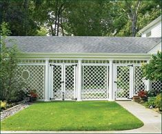 Vinyl Trellis Fence - Diagonal trellis panels are transformed into a protective wall to create an imaginative semi-private breezeway that runs from home to garage. A stylish touch is the oval cut out in one panel, while functionality is displayed by the matching single and double entrance gates.
