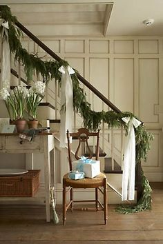 Christmas decor for the banister: swag/garland with white ribbons along the staircase.