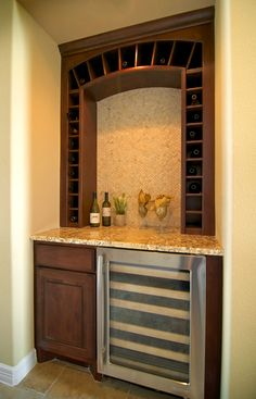 custom dry bar with built in wine cooler and bottle storage with granite counter & raised panel doors.