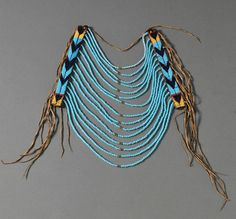Northern Plains Beaded Commercial Leather and Hide Loop Necklace,  | Multicolored chevron design and strands of large light blue beads, fringe down both sides | ca. late 19th century | 1920$ ~ Sold
