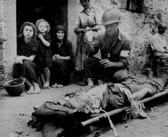 El soldado con funciones de auxiliar médico de campo Harvey White administra plasma sanguíneo a su camarada Roy Humphrey bajo la mirada de civiles italianos, Sicilia, 9 de agosto de 1943