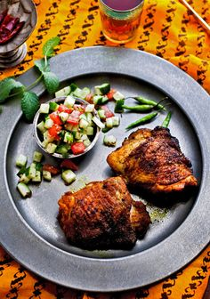 Spice-rubbed grilled chicken thighs with tomato-cucumber relish. Photo: Andrew Scrivani for The New York Times