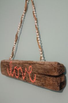 Cute driftwood sign with the word love written on it, and pearls.