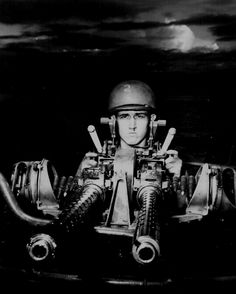 """A PT marksman provides a striking camera study as he draws a bead with his 50 caliber machine gun on his boat off New Guinea."" July 1943."