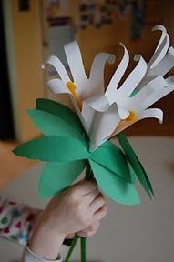 Trace your hand on white paper and cut out.Take  short length orange pipe cleaner,twist it to the end of a long green pipe cleaner so the ens stick up like a V with droopy ears. This is flowers center.      Wrap the hand print around the top of the green pipe cleaner and tape      Poke hole in middle of  double leaves  thread onto  pipe cleaner       Wrap tape around stem below