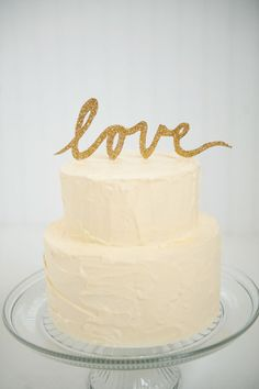 Gold glitter LOVE script wedding cake topper. $20.00, via Etsy.