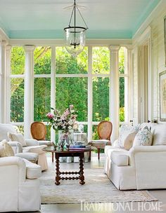 """Cream sofa and chairs from Waterfall Charles of London set a relaxed mood in the glassed-in porch next to the living room. The ceiling is painted """"Bird's Egg"""" by Benjamin Moore.   Sources: Windows: original to house. Wall paint (""""Marble White"""" #OC-34); blue ceiling paint (""""Bird's Egg"""" #2051-60): Benjamin Moore & Co., benjaminmoore.com. Hanging lantern (""""Bell Jar Chandelier""""): Lamp Arts Inc., lampartsinc.com."""