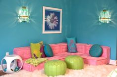 In the seating area, beaded sconces flank a pink tufted sofa which sits directly on the floor. Lime green Moroccan poufs serve as a makeshift coffee table.