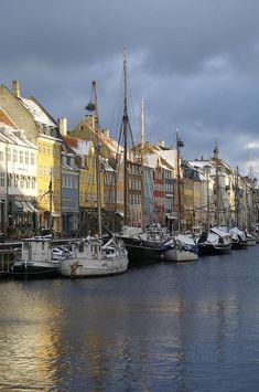 Denmark, Copenhagen, Nyhavn, boats moored on waterfront, frozen canal, yule trees on chimmey tops