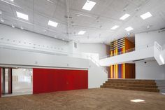 The Vibeeng School / Arkitema Architects, commons gym, red operable partition, forum, stair, wood floor, square skylights, tectum ceiling tile