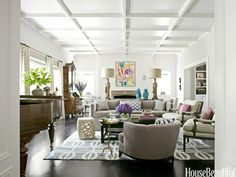 """Move Seating Away From the Walls: """"Float furniture away from the walls: It creates more intimate seating,"""" designer Betsy Burnham says. She did just that in the living room of this California house. The console table separating back-to-back sofas is decked with vintage goddess figurine lamps and Chinese monkeys """"for a Tony Duquette, William Haines flavor."""