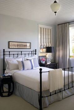 Blue and white bedroom ... striped roman shades and drapery ... black wrought iron bed ... beadboard painted white ceiling ... vintage light fixture.