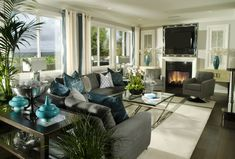 Grey and white living room design with splashes of blue.  Fireplace and television on one end illuminated with plenty of natural light from ...