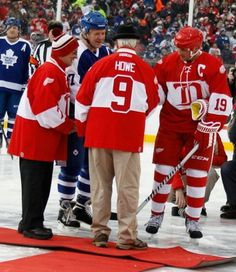 Detroit Red Wing alumni Mickey Redmond, Gordie Howe greet Toronto's Shayne Corson and Detroit's Steve Yzerman at center ice for the ceremonial puck drop to start the second game at the Alumni Showdown between the Detroit Red Wings and Toronto Maple Leafs at Comerica Park.