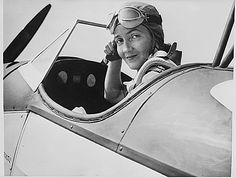 Mrs. Nancy Harkness Love, 28, director of the U.S. Women's Auxiliary Ferry Squadron, adjusts her helmet in the cockpit of an Army plane before taking off from an eastern United States base. The women under her command will ferry planes from factories to coastal airports, from which they will be flown to overseas battle fronts. (National Archives, Record Group 208, ARC 535775)