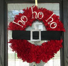 """Wreath hand cut and hand tied from red burlap strips, measures 24"""" across. Letters are wood painted white with glitter. Belt is constructed from black burlap and decorated with glittery belt buckle."""