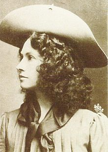 Annie Oakley (1860-1926), born Phoebe Ann Mosey, was an American sharpshooter and exhibition shooter. As she was becoming known, Frank Butler, a traveling show marksman, had bet he could beat any local fancy shooter.  He lost to Oakley but began courting her.  They married on June 20, 1882.  Oakley's amazing talent and timely rise to fame led to a starring role in Buffalo Bill's Wild West show, which propelled her to become the first American female superstar.  Oakley's most famous trick is p...