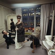 A woman shops for a fur coat at Bergdorf Goodman in New York City. Her Chinese pug, Miss Puffet, sits on a nearby chaise. December 1964. Thi...