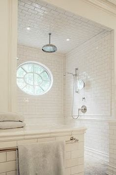 I love the big, round window in this pristine white subway tile shower.  No door needed bc it's a rain shower head